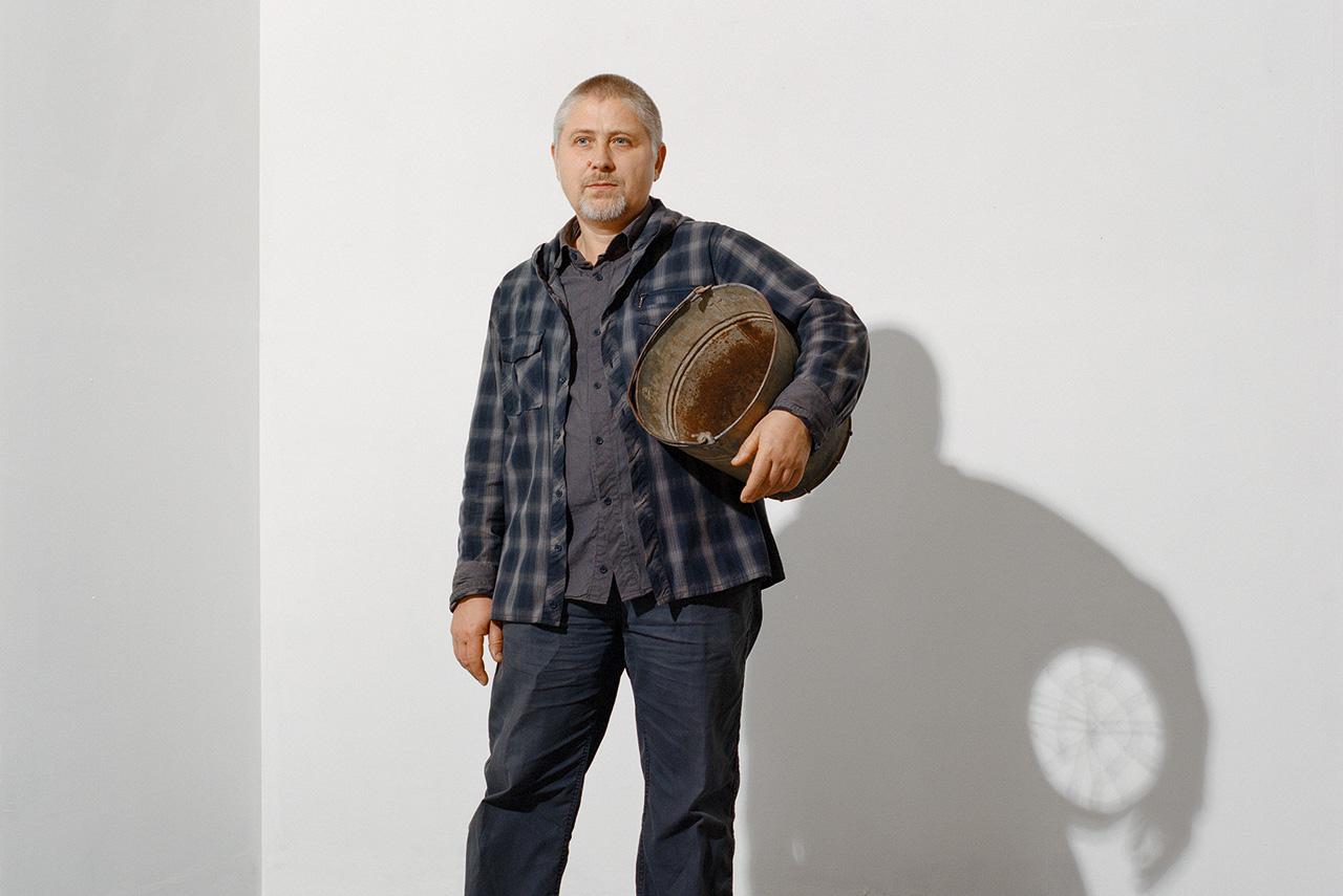 Художник и куратор Владимир Архипов позирует с экспонатом собственной выставки — ведром, у которого вместо дна велосипедное колесо