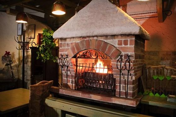 Ресторан Малахит - фотография 1 - Камин в зале ресторана, на котором готовят шашлык, мясо на углях и т.п.
