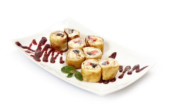 Ресторан Вкуснолюбов - фотография 26 - Сливочный ролл с клубникой, бананом и виноградом со сметанным кремом под ягодным соусом.